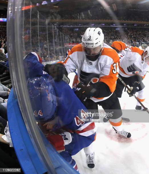 Radko Gudas of the Philadelphia Flyers checks Neal Pionk of the New York Rangers into the boards during the second period at Madison Square Garden on...