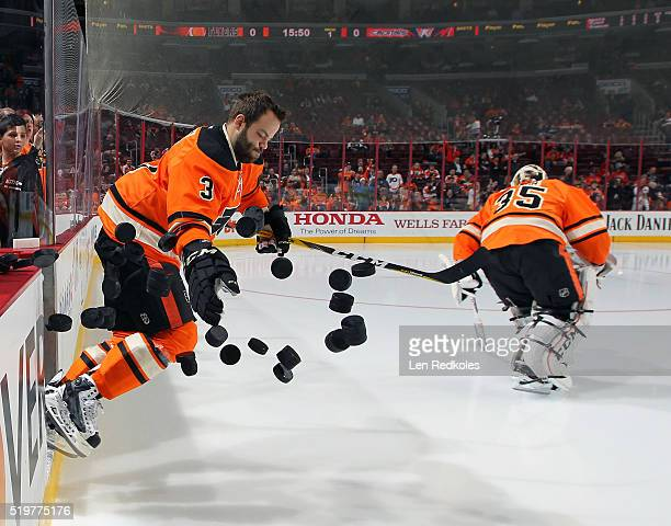 Radko Gudas of the Philadelphia Flyers dumps the practice pucks to the ice for the pregame warmups prior to his game against the Washington Capitals...