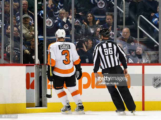 Radko Gudas of the Philadelphia Flyers gets escorted off the ice by linesman David Brisebois after receiving a major penalty and a game misconduct...