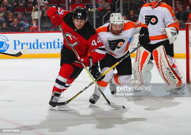 Radko Gudas of the Philadelphia Flyers playing in his 300th NHL game and Miles Wood of New Jersey Devils battle for position during the game at...