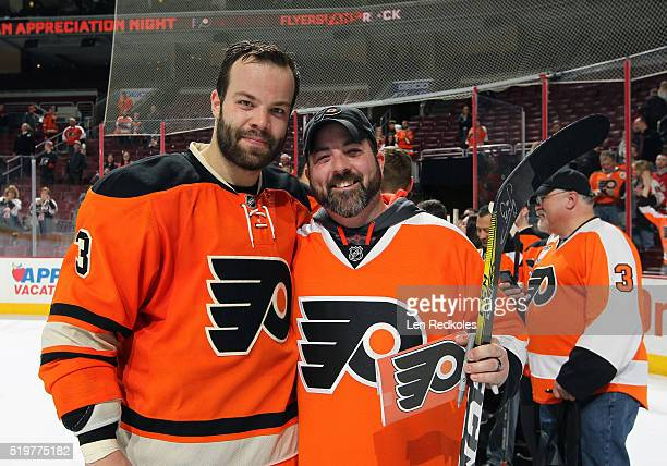 Radko Gudas of the Philadelphia Flyers poses with a fan during a postgame event for Fan Appreciation Night after defeating the Washington Capitals 21...