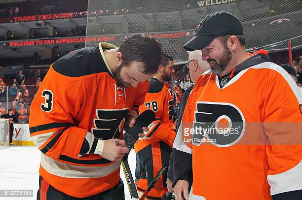 Radko Gudas of the Philadelphia Flyers signs his stick for a fan during a postgame event for Fan Appreciation Night after defeating the Washington...