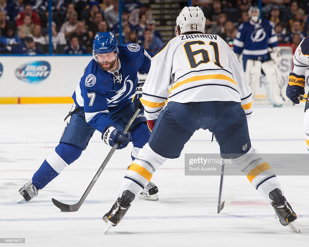 Radko Gudas #7 of the Tampa Bay Lightning carries the puck against Nikita Zadorov #61 of the Buffalo Sabres during the third period at the Tampa Bay Times Forum on October 26, 2013 in Tampa, Florida.