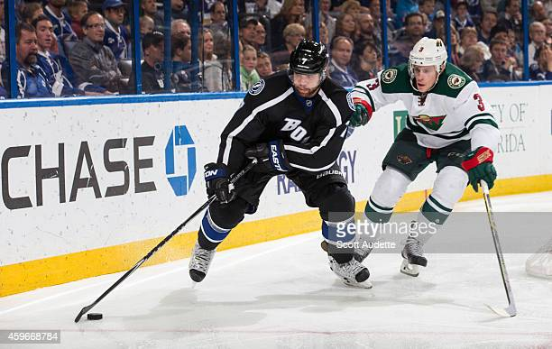 Radko Gudas of the Tampa Bay Lightning controls the puck against Charlie Coyle of the Minnesota Wild during the third period at the Amalie Arena on...