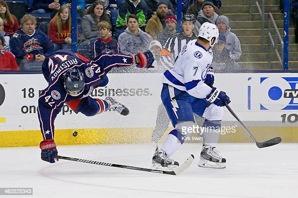 Radko Gudas of the Tampa Bay Lightning knocks Artem Ansimov of the Columbus Blue Jackets off his feet while chasing after the puck during the second...