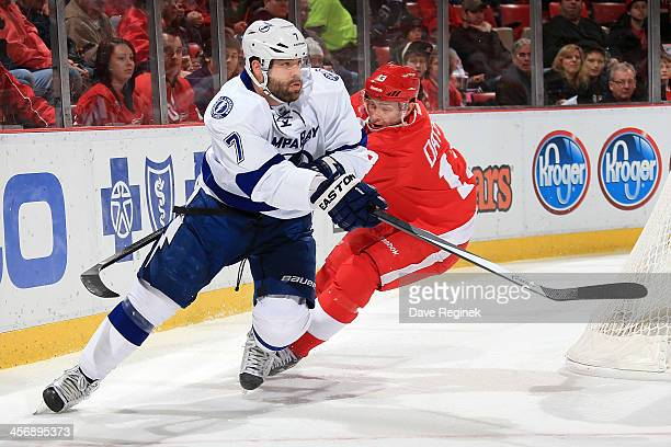Radko Gudas of the Tampa Bay Lightning passes the puck just as Pavel Datsyuk of the Detroit Red Wings tries reach around to lift his stick during an...