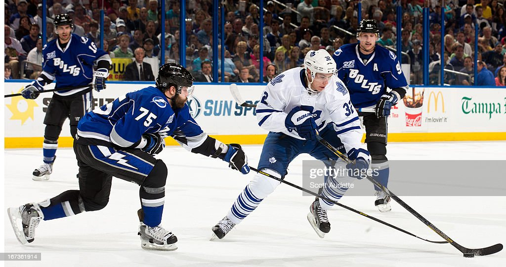 Radko Gudas #75 of the Tampa Bay Lightning reaches for the puck over Joe Colborne #32 of the Toronto Maple Leafs during the second period of the game at the Tampa Bay Times Forum on April 24, 2013 in Tampa, Florida.
