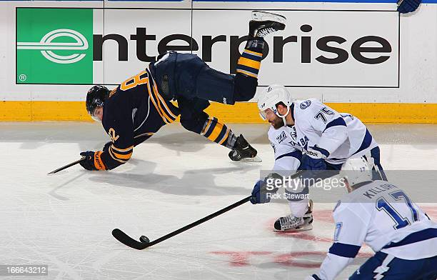 Radko Gudas of the Tampa Bay Lightning skates with the puck as Marcus Foligno of the Buffalo Sabres falls at First Niagara Center on April 14 2013 in...