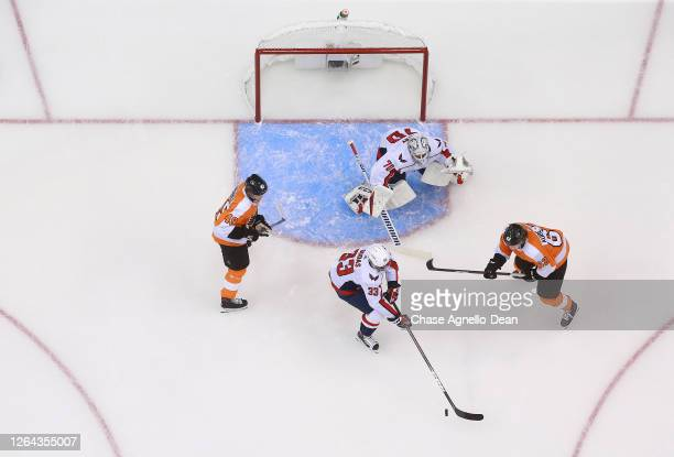 Radko Gudas of the Washington Capitals controls the puck in the slot area as Nicolas AubeKubel of the Philadelphia Flyers looks on during the first...