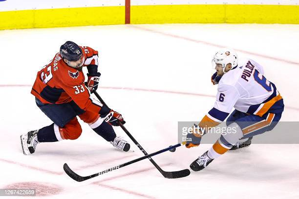 Radko Gudas of the Washington Capitals is defended by Ryan Pulock of the New York Islanders during the second period in Game Five of the Eastern...