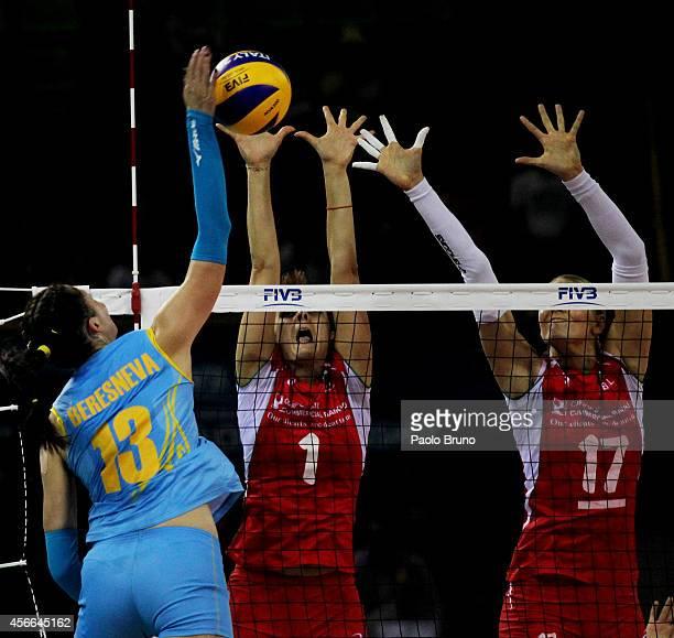 Radmila Beresneva of Kazakhstan spikes the ball as Diana Nenova and Filipova Strashimira during the FIVB Women's World Championship pool F match...