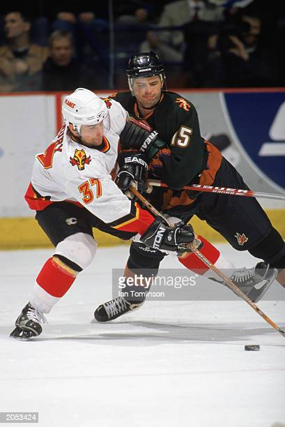 Radoslav Suchy of the Phoenix Coyotes and Dean McAmmond of the Calgary Flames scramble for control of the puck during the game at Pengrowth...