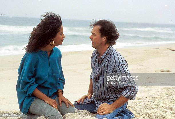 Rae Dawn Chong and Michael Keaton sitting in the sand together at the beach in a scene from the film 'The Squeeze' 1987