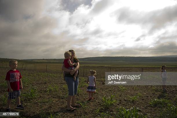 Rae Dawn Dock holds her son Bentley while her daughters Brinley Miley and son Colby listen to the service at the Flight 93 National Memorial during...