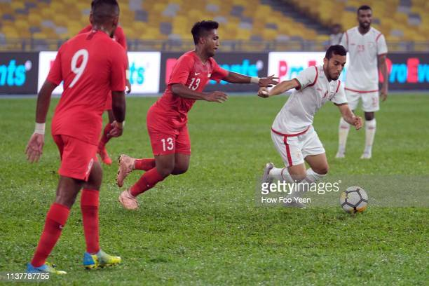 Raed Ibrahim Saleh of Oman shields the ball from Muhammad Izzdin Shafiq of Singapoe during the Airmarine Cup final between Singapore and Oman at...