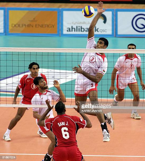 Raed Said alHashemi of Oman spikes the ball against UAE player Sami Jassem at the 17th Arabian volleyball Gulf Cup tournament at alRayyan court 16...