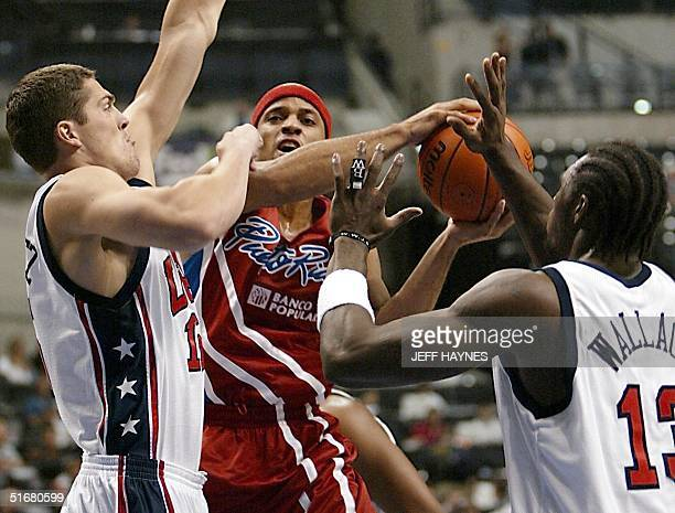 Raef LaFrentz and Ben Wallace of the US try to block the shot of Elias Ayuso of Puerto Rico 06 September 2002 during the first half of their...