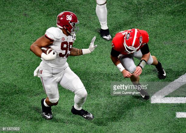 Raekwon Davis of the Alabama Crimson Tide runs with an interception against Jake Fromm of the Georgia Bulldogs in the CFP National Championship...