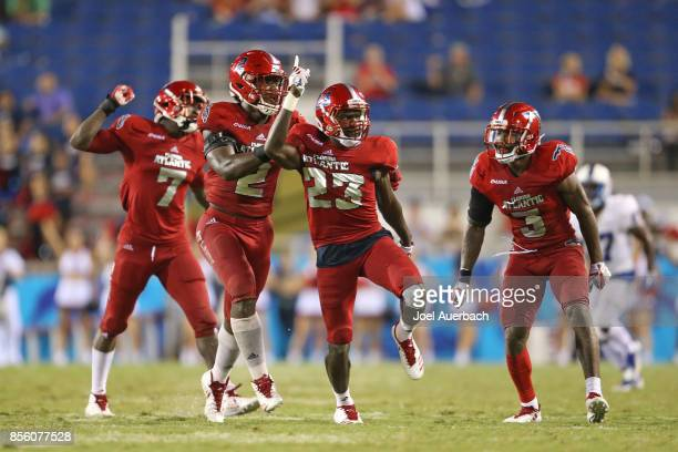 Raekwon Williams of the Florida Atlantic Owls is congratulated by teammates after intercepting a pass thrown by the Middle Tennessee Blue Raiders on...