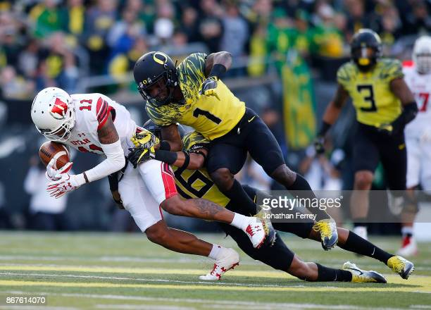 Raelon Singleton of the Utah Utes is tackled by Arrion Springs and Nick Pickett of the Oregon Ducks at Autzen Stadium on October 28 2017 in Eugene...