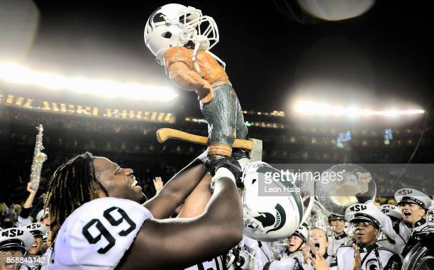 Raequan Williams of the Michigan State Spartans celebrates a win over the Michigan Wolverines and carries the Paul Bunyan trophy after the game at...