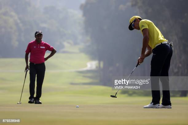 Rafa Cabrera Bello of Spain makes a putt as SSP Chawrasia of India watches on the ninth green during the final round of the Hong Kong Open golf...