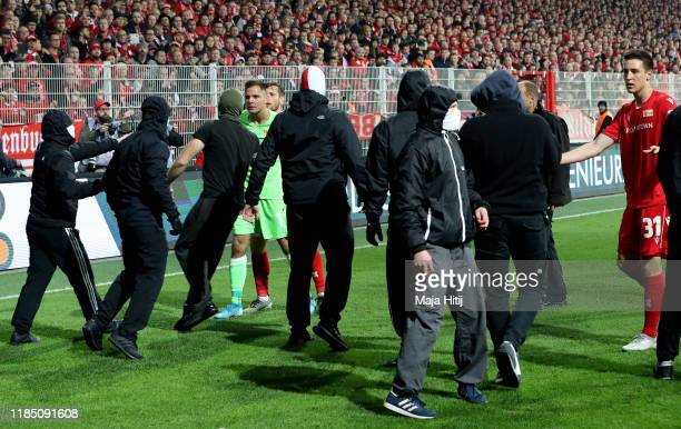 Rafa Gikiewicz of 1 FC Union Berlin and teammates attempt to get supporters off the pitch during the Bundesliga match between 1 FC Union Berlin and...