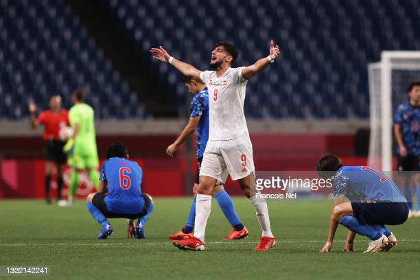 Rafa Mir of Team Spain celebrates their side's victory as the players of Team Japan look dejected after the Men's Football Semi-final match between...