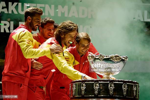 Rafa Nadal of Spain celebrates the victory with the trophy next to his teammates in the Final between Spain and Canada during Day Seven of the 2019...