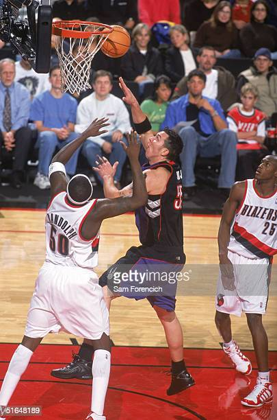Rafael Araujo of the Toronto Raptors goes to the basket against Zach Randolph of the Portland Trail Blazers during a preseason game at The Rose...