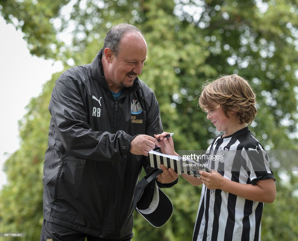 Rafael Benitez (L) signs an autograph for a fan during the Newcastle United Training session at Carton House on July 12, 2018, in Kildare, Ireland.