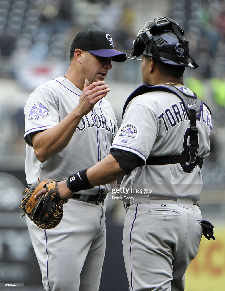 Rafael Betancourt #63 of the Colorado Rockies (L) is congratulated by Yorvit Torrealba #8 after getting the final out during the ninth inning of a baseball game against the San Diego Padres at Petco Park on April 14, 2013 in San Diego, California. The Rockies won 2-1.