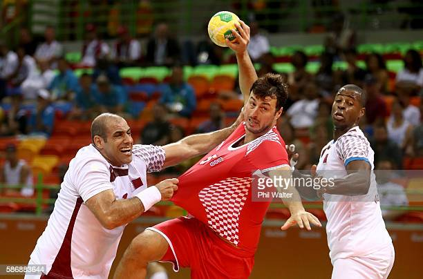 Rafael Capote and Bassel Alrayes of Qatar try to hold back Domagoj Duvnjak of Croatia during the Men's Preliminary Group A match between Croatia and...