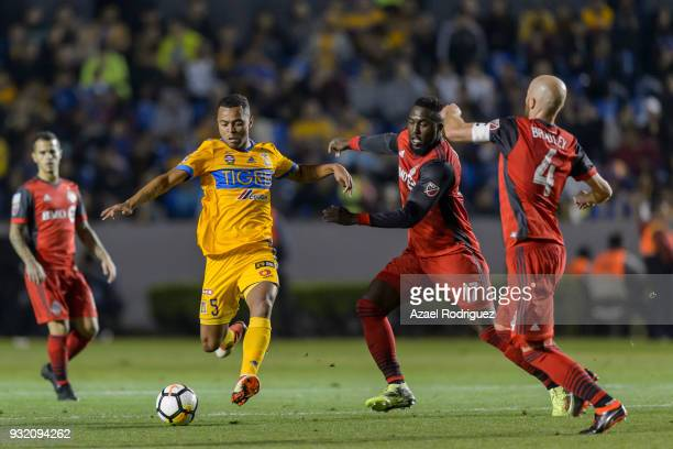 Rafael De Souza of Tigres fights for the ball with Jozy Altidore and Michael Bradley of Toronto during the quarterfinals second leg match between...