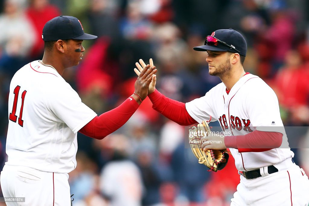 Rafael Devers #11 high fives Andrew Benintendi #16 of the Boston Red Sox after a victory over the Baltimore Orioles at Fenway Park on April 14, 2018 in Boston, Massachusetts.