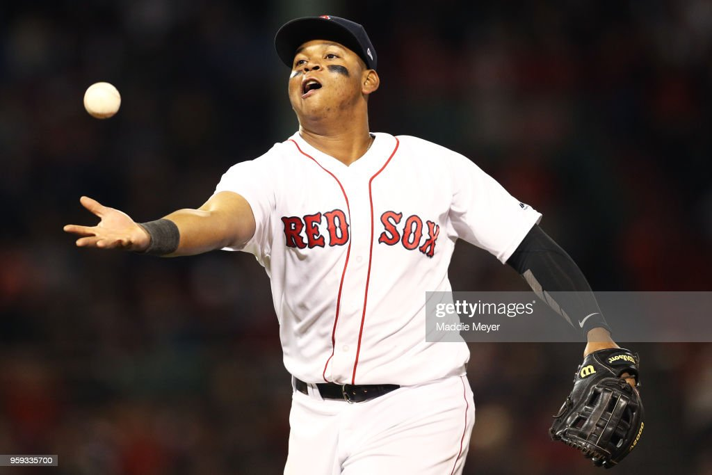 Rafael Devers #11 of the Boston Red Sox catches a ball tossed to him by Eduardo Nunez #36 after the eighth inning at Fenway Park on May 16, 2018 in Boston, Massachusetts.