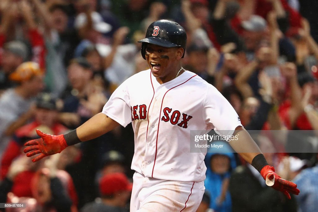 Rafael Devers #11 of the Boston Red Sox celebrates after hitting an inside the park home run in the ninth inning against the Houston Astros during game four of the American League Division Series at Fenway Park on October 9, 2017 in Boston, Massachusetts.