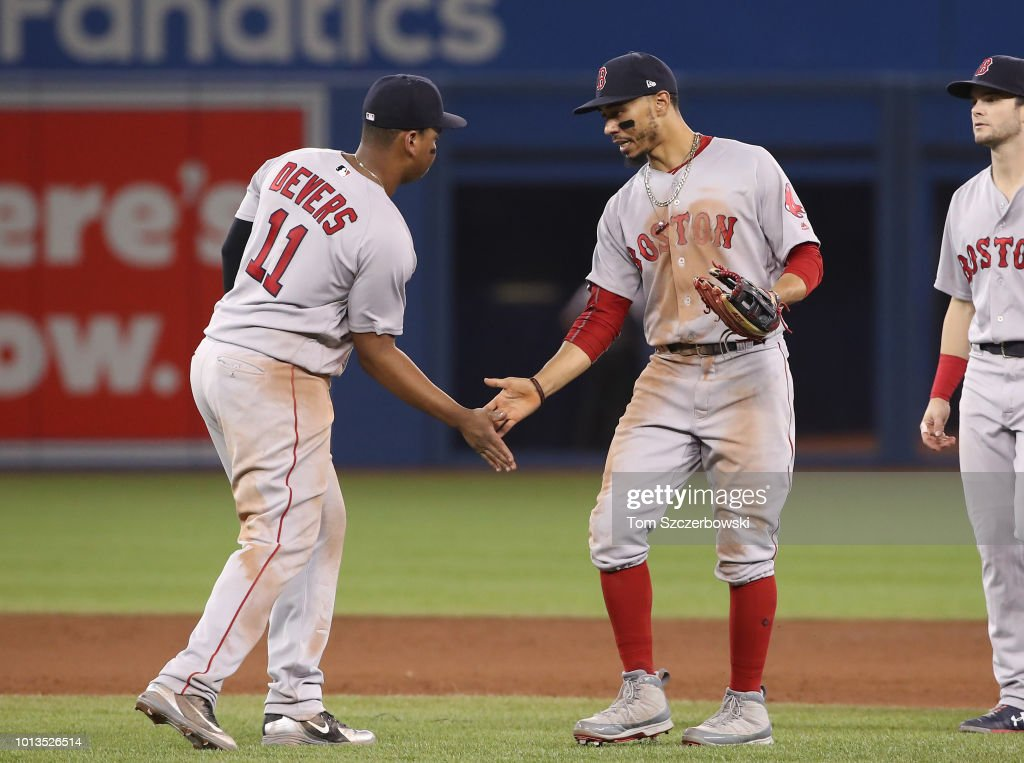 Rafael Devers #11 of the Boston Red Sox celebrates their victory with Mookie Betts #50 during MLB game action against the Toronto Blue Jays at Rogers Centre on August 8, 2018 in Toronto, Canada.