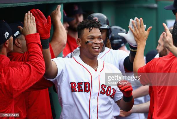 Rafael Devers of the Boston Red Sox celebrates with teammates in the dugout after hitting a tworun home run in the third inning against the Houston...