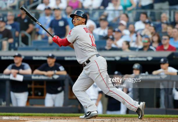 Rafael Devers of the Boston Red Sox follows through on a first inning grand slam home run against the New York Yankees at Yankee Stadium on June 30...