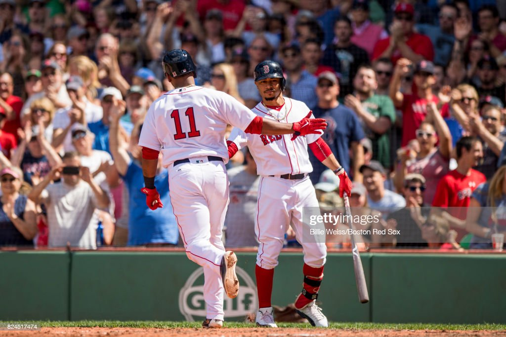 Rafael Devers #11 of the Boston Red Sox high fives Mookie Betts #50 after hitting a solo home run during the fifth inning of a game against the Kansas City Royals on July 30, 2017 at Fenway Park in Boston, Massachusetts.