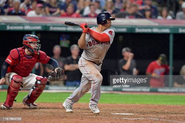 Rafael Devers of the Boston Red Sox hits a double during the tenth inning against the Cleveland Indians at Progressive Field on August 13 2019 in...