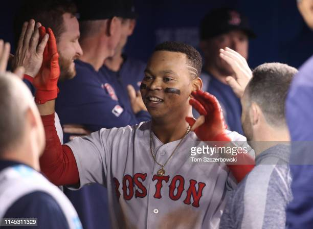 Rafael Devers of the Boston Red Sox is congratulated by teammates in the dugout after hitting a solo home run in the ninth inning during MLB game...