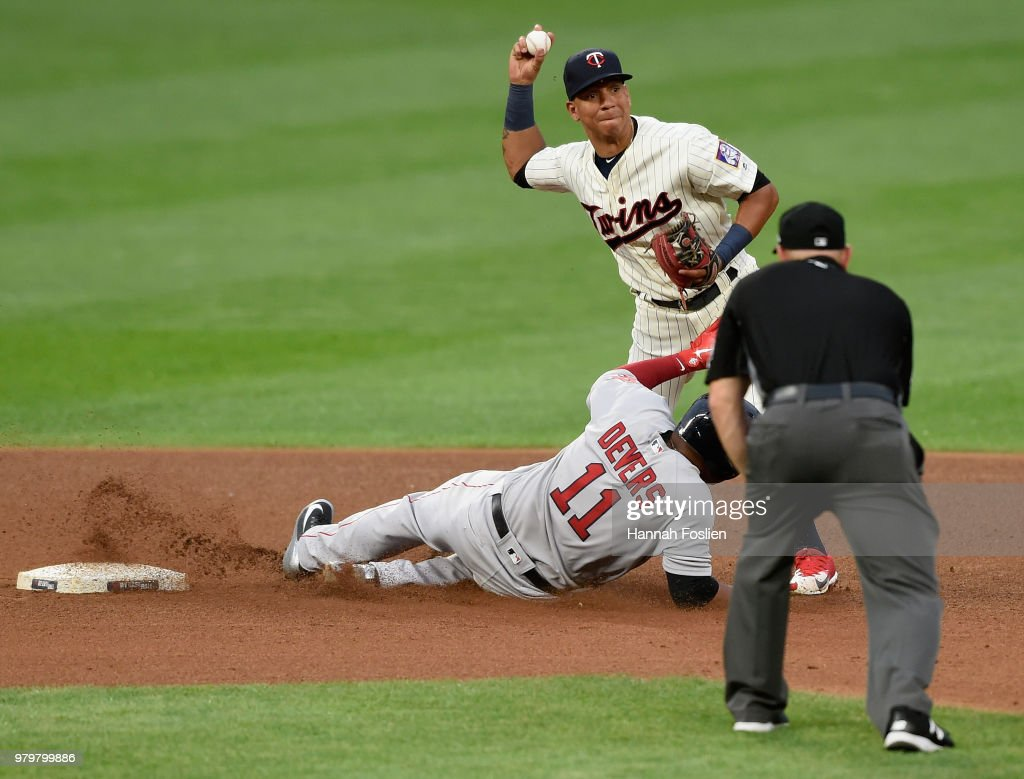 Rafael Devers #11 of the Boston Red Sox is out at second base as Ehire Adrianza #16 of the Minnesota Twins turns a double play and umpire Scott Barry #87 looks on during the fourth inning of the game on June 20, 2018 at Target Field in Minneapolis, Minnesota.