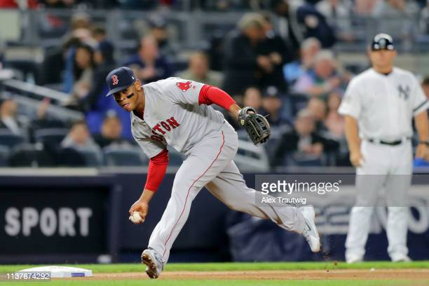 Rafael Devers of the Boston Red Sox makes a bare handed play during the game between the Boston Red Sox and the New York Yankees at Yankee Stadium on...