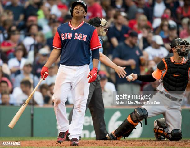 Rafael Devers of the Boston Red Sox reacts after a swing and miss against the Baltimore Orioles in the seventh inning at Fenway Park on August 26...