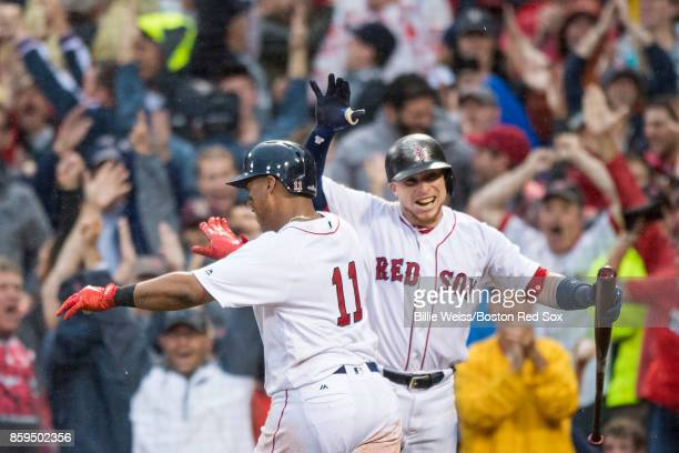 Rafael Devers of the Boston Red Sox reacts with Christian Vazquez after hitting an inside the park home run during the ninth inning of game four of...