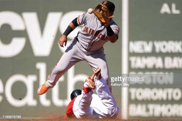 Rafael Devers of the Boston Red Sox safely avoids the tag from Christhian Adames of the San Francisco Giants in the second inning at Fenway Park on...