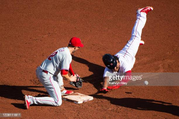 Rafael Devers of the Boston Red Sox safely slides into second after hitting a double while Neil Walker of the Philadelphia Phillies is unable to make...