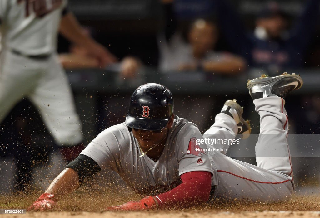 Rafael Devers #11 of the Boston Red Sox slides safely into home plate to score a run against the Minnesota Twins during the eighth inning of the game on June 19, 2018 at Target Field in Minneapolis, Minnesota. The Twins defeated the Red Sox 6-2.